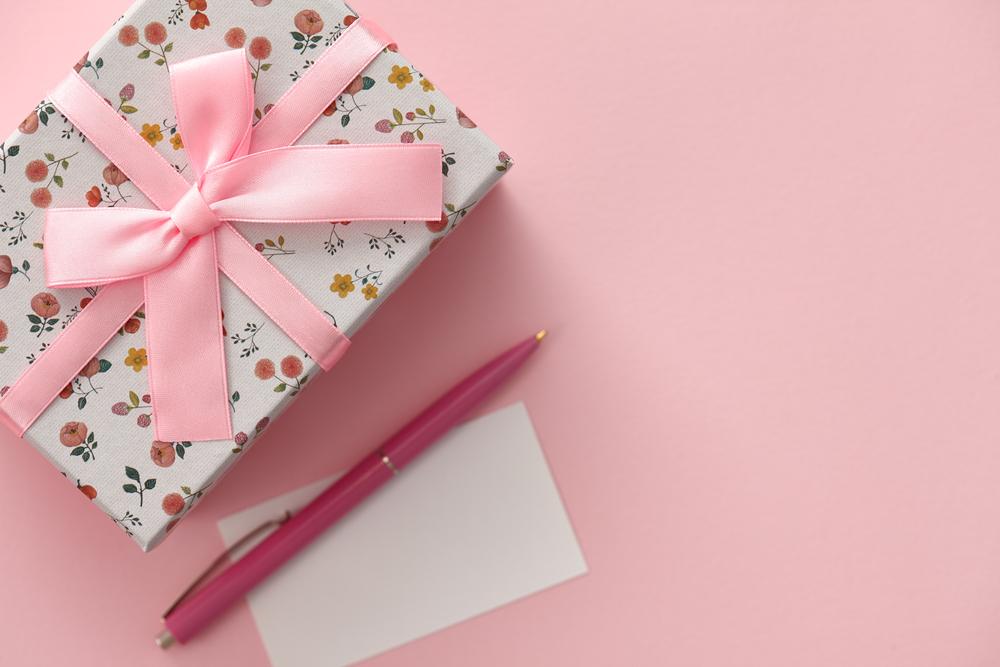 Caixa com estampa florida e laço rosa. Ao lado, um papel branco e uma caneta rosa.